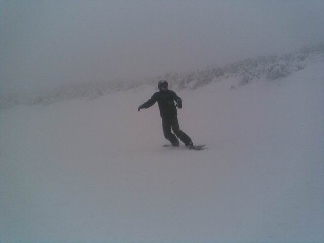 A snowboarder in the fog